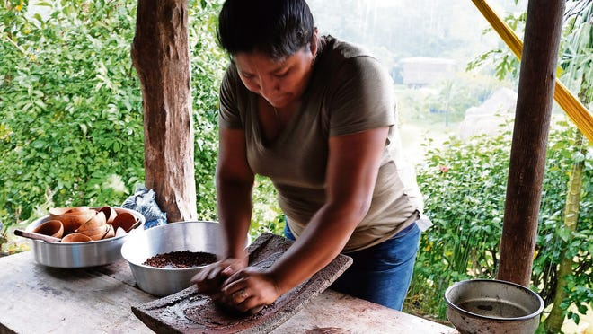 A worker turns processed cacao into a paste.