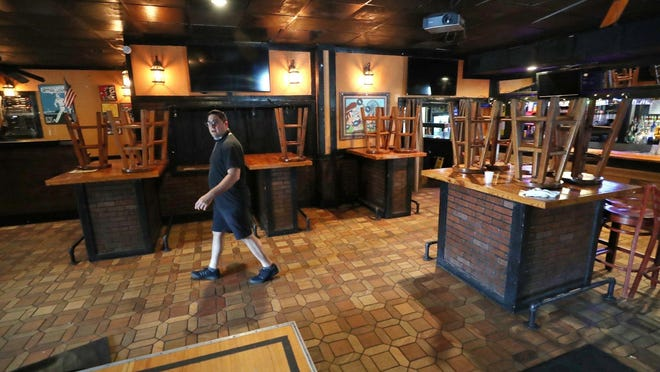 Mario Nemr, who runs Thursday's Lounge, walks to the patio as he talks about the changes to the bar over the years on Aug. 12, 2020 in Akron. Thursday's is closing after 37 years at the end of August.