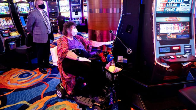 Dorothy McCarthy plays a slot machine as Bobby Lay, Director of Player Development at Ocean Casino Resort, looks on. Ocean Casino Resort in Atlantic City is open for the first time since closing due to the Covid-19 crisis on Thursday, July 2, 2020.