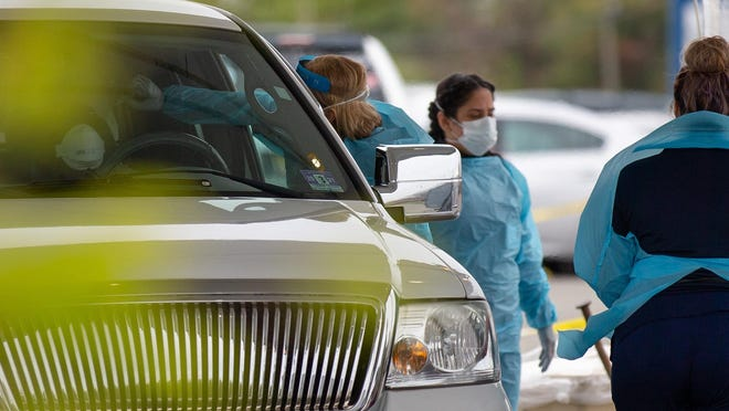 File - A doctor administers a coronavirus test to a patient in a vehicle at Virtua Willingboro.