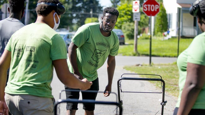 Miguel Tucker, center, helps get the kids going in the Urban Scouts program, a five-week effort where youth receive $13.50 an hour to do landscaping and gardening work in the Linden area while also learning life skills.