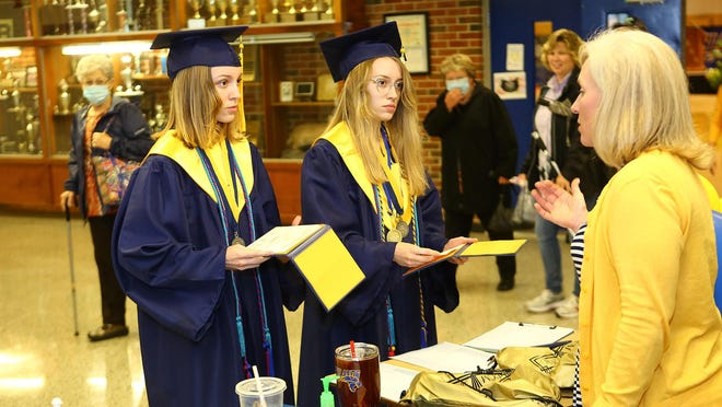 Richlands High School graduates McKenzie Craft, left, and her twin sister Madison Craft received their diplomas Monday afternoon and then joined family for photos to mark the milestone.