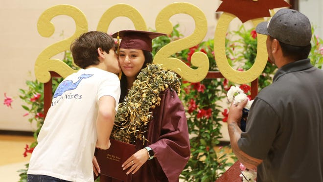 Graduate Lana Watson gets a kiss from her brother Jacob Watson as Shawn Guidry, uncle, looks on. Graduates of Dixon High School accompanied by family and friends received their diplomas then gathered for a few moments to take some special photos.
