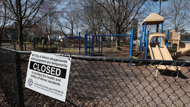 A closed sign hangs on the fence of Akron's Hereford Park and the playground equipment is taped off on March 26. Akron playgrounds are due to reopen Wednesday.