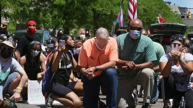Akron Mayor Daniel Horrigan and Deputy Mayor for Public Safety Charles A. Brown kneel with protesters on High Street near East Exchange before walking to the Akron Police Department for a rally Saturday, June 6, 2020.
