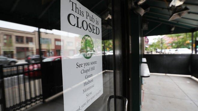 Other businesses are reflected the glass of the front door  of the former Brubaker's Pub  in downtown Akron on Tuesday, June 2, 2020. The sign on the door refers patrons to other Brubaker's Pubs, which remain open.