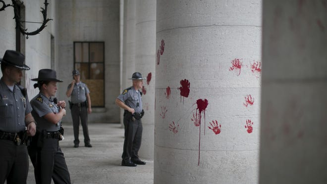 A small group of protesters left red handprints on the Ohio Statehouse on Thursday, June 18, 2020, to signify the blood on police hands, they said.