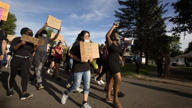 Organizers, including, Kanyinsola Oye, right, a junior at Howard University and Columbus Alternative High School alumni, protest Monday outside Columbus Board of Education President Jennifer Adair's house, asking Columbus City Schools to terminate their contract with the Columbus police.