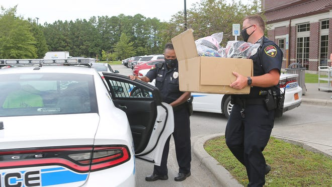 Jacksonville Public Safety Officer Christopher Patrick carries bicycle helmets donated by Onslow Memorial Hospital to the United Way of Onslow CHEW Program, Jacksonville Police Department  and Safe Kids Onslow.
