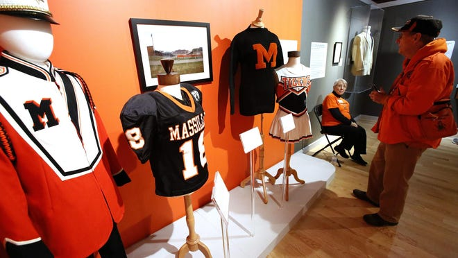 A visitor to the Paul Brown Museum checks out the variety of Massillon Tigers uniforms on display at the museum.