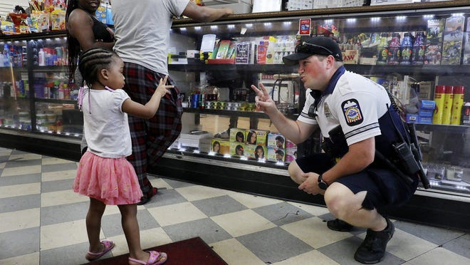 Bike patrol officer T. Roberts asks 3-year-old Ramiya Wright at Fast Fair Foods in Linden on Tuesday, July 14, 2020. Roberts asked that his first name not be used for safety reasons.
