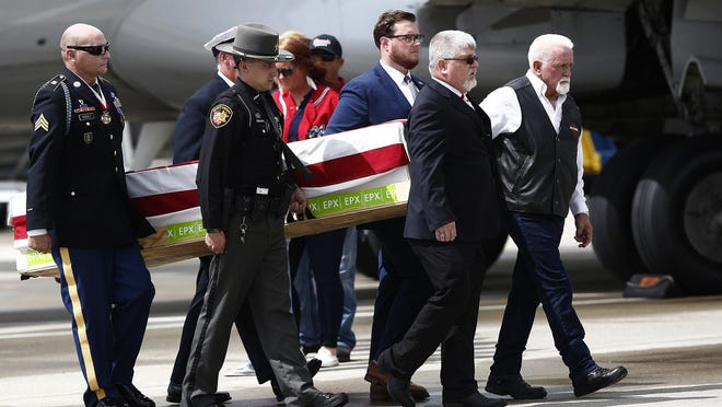 The body of Medal of Honor winner and Columbus native Ronald Rosser is taken from an airplane on Friday, Aug. 28, at John Glenn Columbus International Airport. His brother Larry Rosser, far right, was among the procession. Ronald Rosser earned the award for his actions during the Korean War in 1952. Rosser was 90.