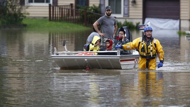 A Columbus fire department rescuer evacuate people from their homes on Stoneshead Court on May 19 after heavy rains pounded the area overnight. If a new model is to be believed, such extreme flooding may affect more central Ohio homes in the future.