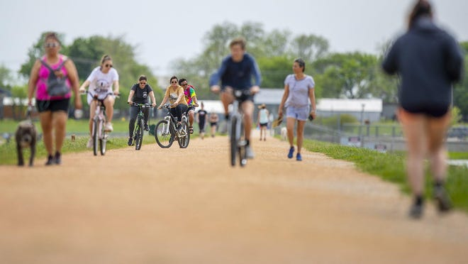 Visitors to Lake Pflugerville enjoy the trail in this March file photo. The trail was closed June 30 but will reopen on Monday.