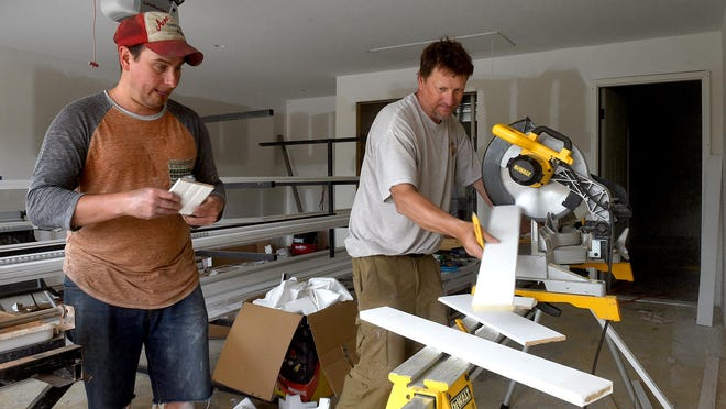 Jon Pearson, left, and Bill Livingston, employees of Corinthian Builders, cut trim pieces for a home under construction at The Vineyards subdivision east of Columbia off Route W.
