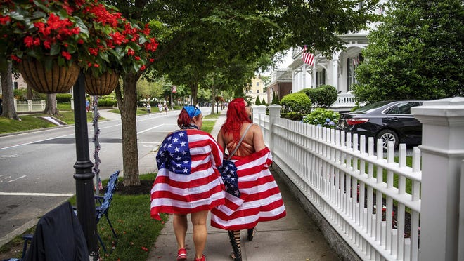 Parade-goers walk down the street before a Fourth of July parade on Saturday, July 4, 2020, in Bristol, R.I. The town, which lays claim to the nation's oldest Independence Day celebration in the country, held a vehicle-only, scaled down version of its annual parade due to the coronavirus pandemic.