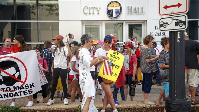 Joy Alice Morrow, of Tulsa, and Alisa Jones, of Bristol, talk while holding signs during a protest against the proposed citywide mask ordinance being voted on by Tulsa City Council at Tulsa City Hall on Wednesday, July 15, 2020.