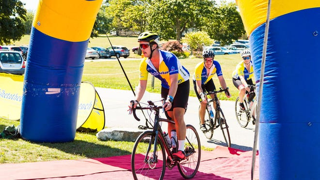 Riders make their way to the finish line Saturday during the Bike to the Beach event that raises money for autism awareness. The ride normally begins in Boston, but because of COVID-19 restrictions, the 100-mile ride started in Woonsocket this year.