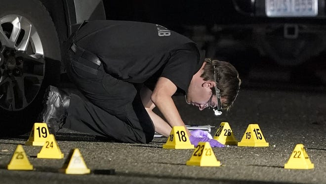 A Washington State Patrol Crime Lab worker looks at evidence markers in the early morning hours of Friday, Sept. 4, 2020, in Lacey, Wash. at the scene where Michael Reinoehl was killed Thursday night as investigators moved in to arrest him. Reinoehl had been suspected of fatally shooting a supporter of a right-wing group in Portland, Oregon, last week after a caravan of Donald Trump backers rode through downtown Portland.