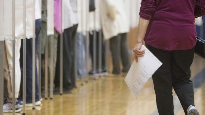 A voter waits to cast a ballot inside the York High School gymnasium in 2019.