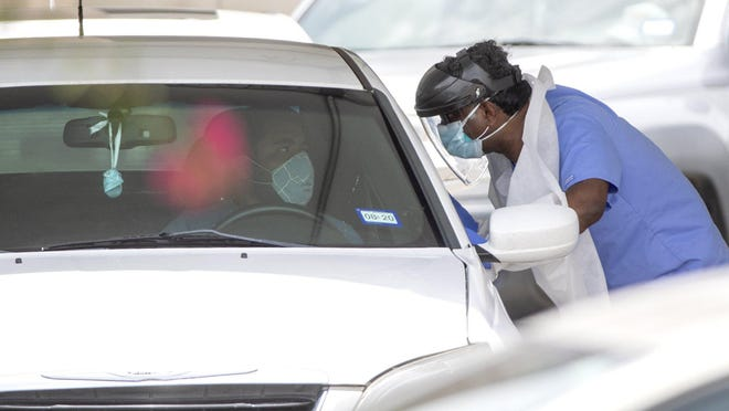 A man is tested for COVID-19 at a drive-through testing site at Community Care at the Hancock Center on June 29, 2020, during the coronavirus pandemic.