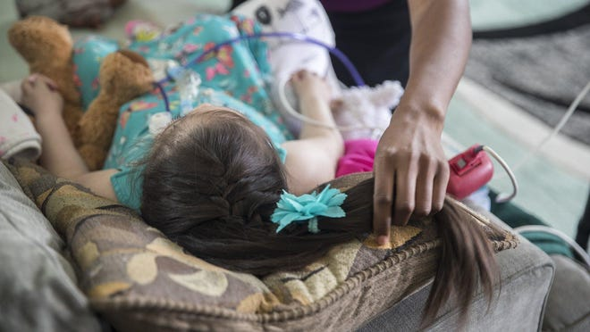 A Child Protective Services worker is shown in 2018 checking on a child receiving medical care at home.