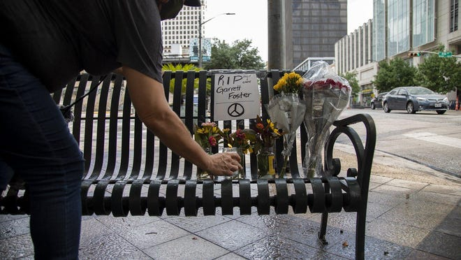 Roxanne Mazariegos leaves flowers for Garrett Foster on Sunday in downtown Austin. Foster was shot and killed Saturday night at Fourth Street and Congress Avenue while attending a protest against police violence.