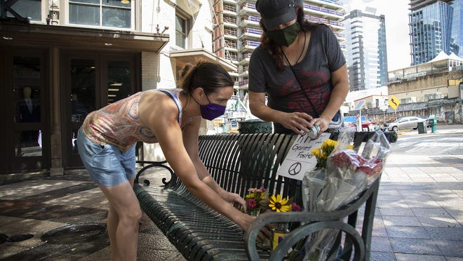 Erica Parkfit, left, and Roxanne Mazariegos leave flowers for Garrett Foster downtown Sunday. Foster was shot and killed Saturday night at Fourth Street and Congress Avenue while attending a protest against police violence.