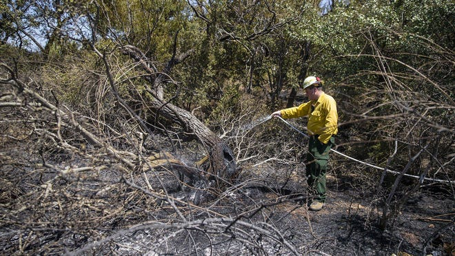 Randall Fuchs of the Texas A&M Forest Service uses a water hose to douse hot spots Friday after a brush fire that started the day before swept across 400 acres in Horseshoe Bay. Homeowners were temporarily evacuated as firefighters worked to contain the blaze.