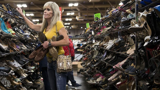 """Patricia Stone shops for shoes at the Settlement Home for Children's Garage & Estate Sale at the Palmer Events Center in 2018. Stone began coming to the sale because her husband has been attending it for nearly 30 years. """"We talk about it all year long, and we love thinking about what we're going to buy"""" Stone said. """"I left with 20 pairs of shoes last year."""""""