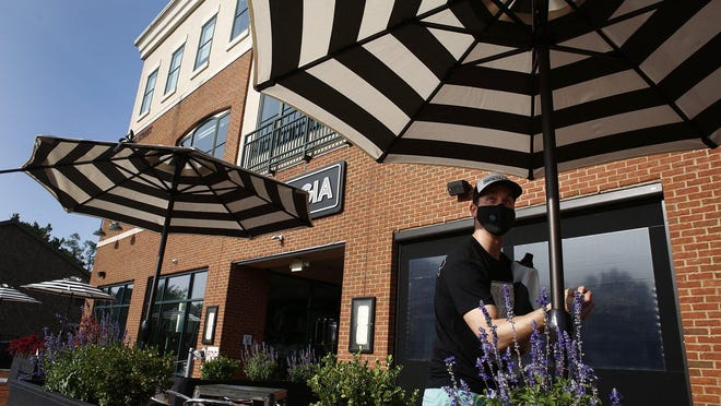 Shawn White, owner of Nostalgia Brewing Company in Gahanna, opens up umbrellas at his business on Thursday. White said Nostalgia doesn't have a dedicated marketing team, so large gatherings are the best way to introduce itself to new customers. Large and small breweries alike are having to find new ways to get their names out there.