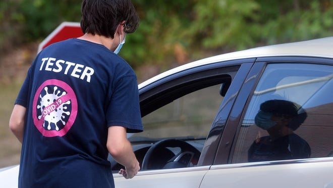 A COVID-19 tester registers people for a drive-through test at UNH on Aug. 24. The number of positive tests for the coronavirus continues to rise in Durham.