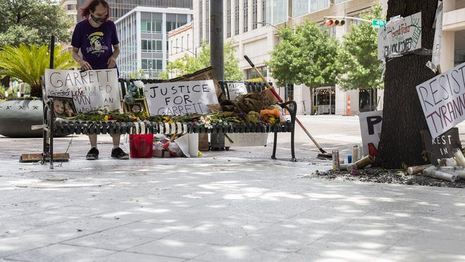 A small group cleans up white paint from Garrett Foster's memorial site in downtown Austin on July 28, 2020. The group, who did not want to be identified, said they  frequented protests against police violence with Foster.  Foster was shot and killed Saturday night on Fourth Street and Congress Avenue while attending a protest. A man who filmed himself on TikTok vandalizing the memorial.