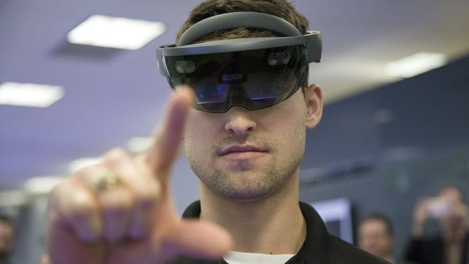 Billy Conte, a media producer at Samsung, demonstrates how to use an augmented reality headset during a tour of the 5G Innovation Zone at Samsung Austin Semiconductor in 2019.