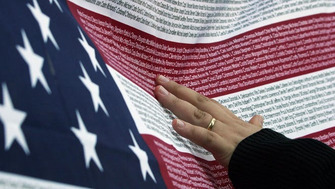 Renata Macedo, a student from Brazil who was studying in New York during the second anniversary of the 9/11 attacks, ran her fingers over an American flag with the names of all the people who died at the World Trade Center during the attacks. Macedo was looking for the name of her friend.