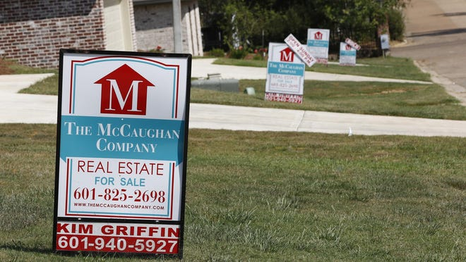 A realty company's signs rest on several lawns in front of newly constructed houses in Brandon, Miss., in September 2019. Mortgage buyer Freddie Mac reports the average rate on the key 30-year loan declined to 3.13% from 3.21% this week.