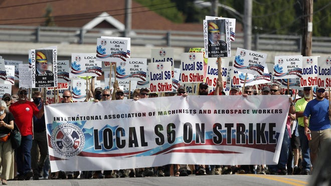 Striking Bath Iron Works shipbuilders march in solidarity, Saturday, July 25, 2020, in Bath, Maine. The union representing striking production workers says a tentative agreement was reached with Navy shipbuilder Bath Iron Works to end a strike that stretched for more than a month.