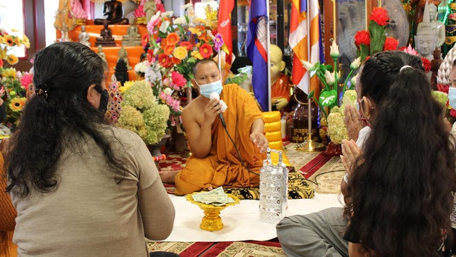A monk prays over two families offerings of food and money during celebrations of Pchum Ben at Dhamagosnaram Buddhist Temple in Cranston on Sunday. Pchum Ben is an annual celebration among Cambodians to celebrate their ancestors and deceased friends and relatives.