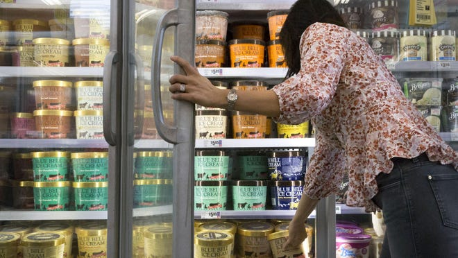 A customer reaches for a gallon of Blue Bell ice cream at a grocery store in Austin in 2018.