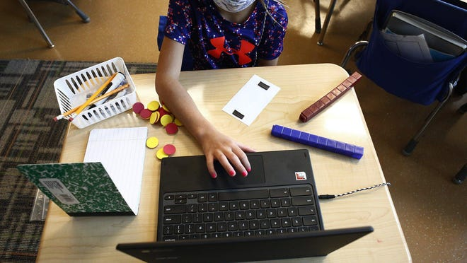 A first grader wearing a mask works on a computer at Richard Avenue Elementary School in Grove City on the second day of hybrid schooling on Wednesday, September 9, 2020.