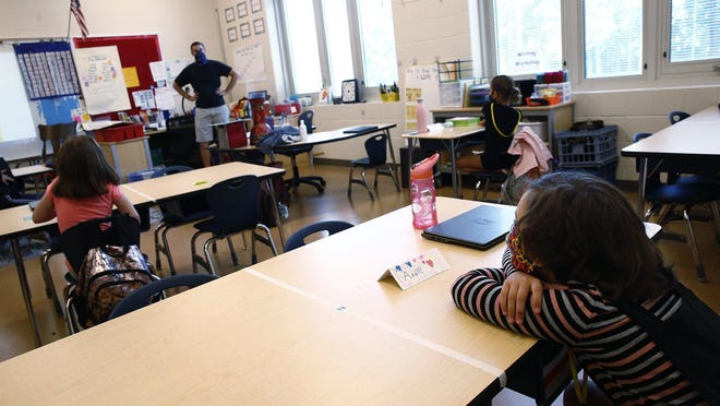 Second-graders were seated apart from one another at Richard Avenue Elementary School in Grove City on the second day of hybrid schooling in the South-Western school district in September. In front of the class is music teacher Spencer Kocher.