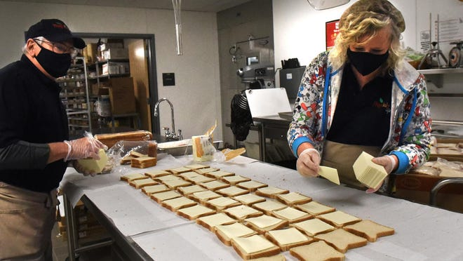 Dover High School food service workers Dave Anderson and Sue Williams work together on creating more than 300 sandwiches for students who need them.