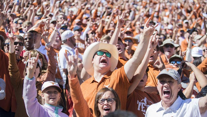 Texas Longhorns fans cheer on the Texas Longhorns after a score against Oklahoma Sooners during an NCAA college football game at the Cotton Bowl on Saturday, Oct. 12, 2019, in Dallas, Texas. This game makes up the114th rivalry match up. RICARDO B. BRAZZIELL / AMERICAN-STATESMAN