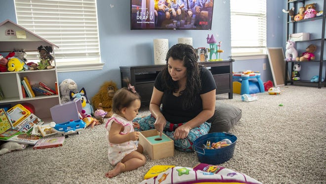 Austin district teacher Alyssa Baird plays with her 1-year-old daughter Elliana after first taking a shower and washing her clothes after returning home from the classroom Thursday. Unable to get accommodations to teach remotely, Baird resigned from her job.