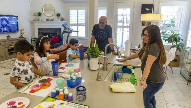 Luz and Martha Perez are shown in March joking with their children Alec, Alexia and Aiden as they paint in the kitchen. The coronavirus restrictions have meant more family time in many households.