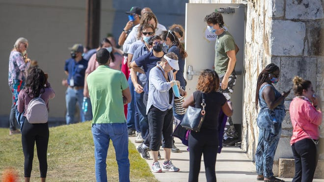 People wait in line for a little over an hour to vote at the Pflugerville ISD Rock Gym on Friday, Oct. 16, 2020.