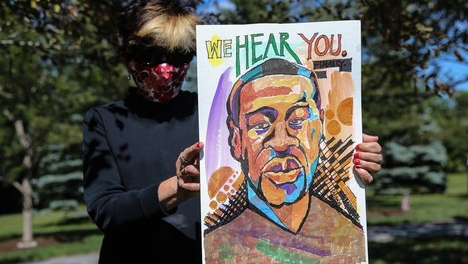 Marianne Orlando, of Framingham, holds a portrait she painted of George Floyd during a Black Lives Matter event at Cushing Memorial Park in Framingham on Sunday.
