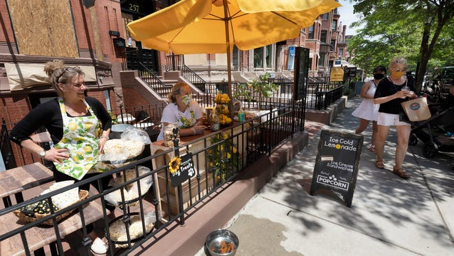 Tracy Casavant, left, owner of Bittersweet Shoppe on Newbury Street, sells lemonade with Cheryl Johnson, Saturday, June 6, in Boston. Gov. Charlie Baker has announced that retail stores, restaurants and hotels will be allowed to serve customers on Monday as the state moves to Phase 2 of reopening businesses that were shut due to concern about COVID-19.