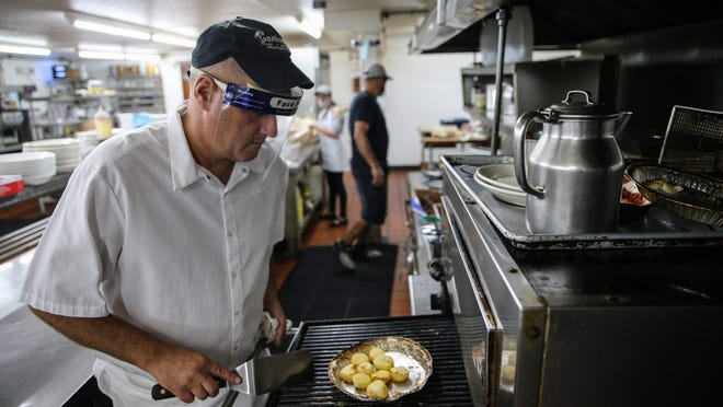 Head chef -- and 33-year employee -- John Marcoux prepares scallops Wednesday evening at Carbone's Restaurant. Carbone's is closing its doors after 87 years in business.