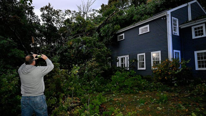 Dan Ferrick, of Old Sudbury Road in Wayland, uses his cellphone to take a picture after a large tree fell on his home during Wednesday night's thunderstorm. Ferrick said the house was built circa 1830 and once belonged to the famous 19th-century abolitionist Lydia Marie Child.